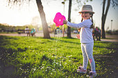 Lovely and cute toddler girl enjoying her time in the park in spring.