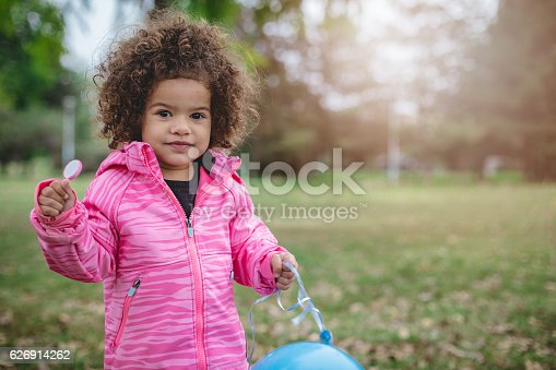 istock Cute toddler with afro hair, holding lollipop 626914262