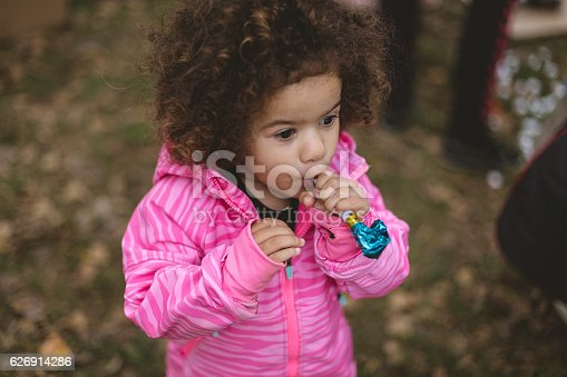 istock Cute toddler with afro hair using party horn 626914286