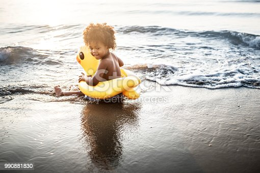 Cute toddler with duck tube on the beach