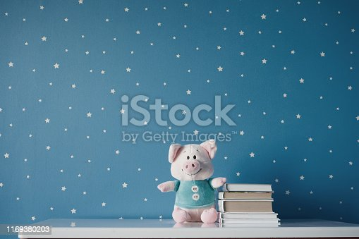 istock cute toy pig and books on the table 1169380203
