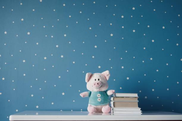 lindo cerdo de juguete y libros en la mesa - foto de stock