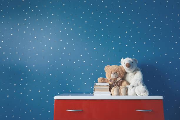 juguetes lindos y libros en la mesa - foto de stock