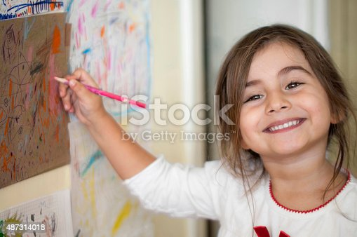 A little girl painting pictures in her room