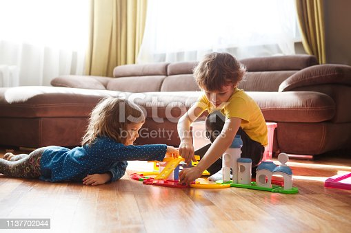 Cute two little children playing with toys at home