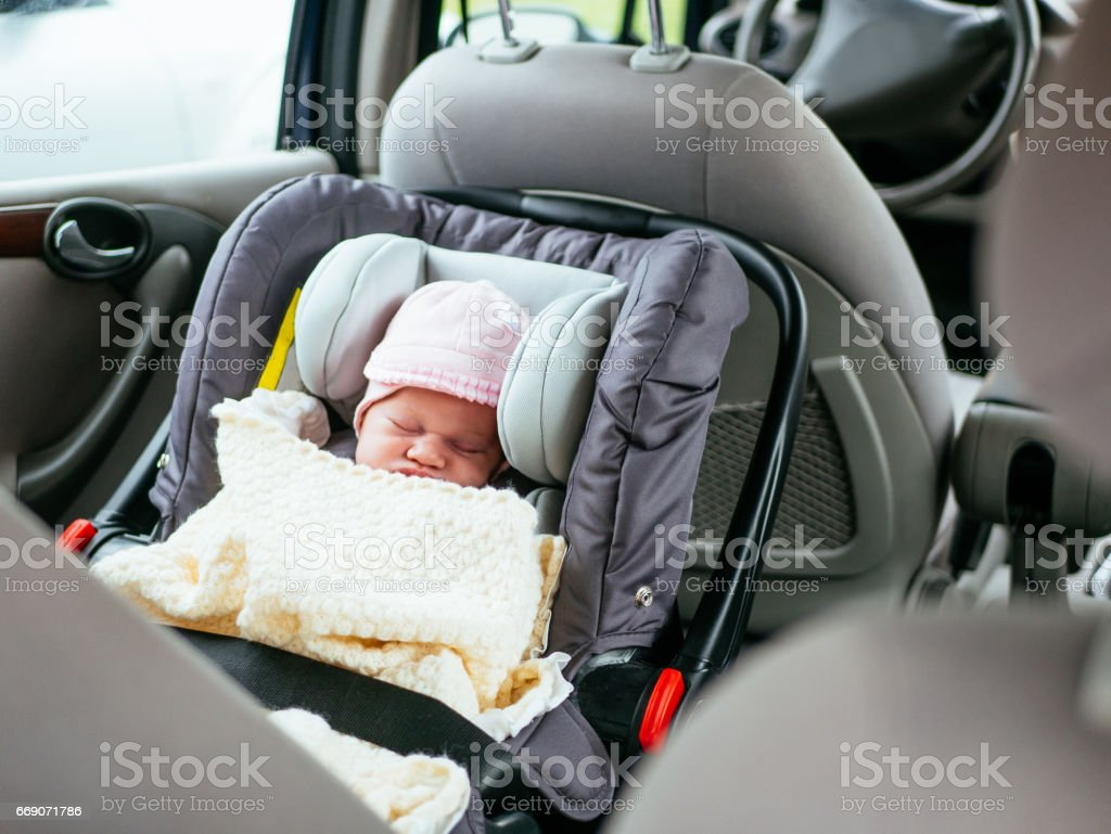 Cute two week old baby sleeping in car seat on back-seat of the car stock photo