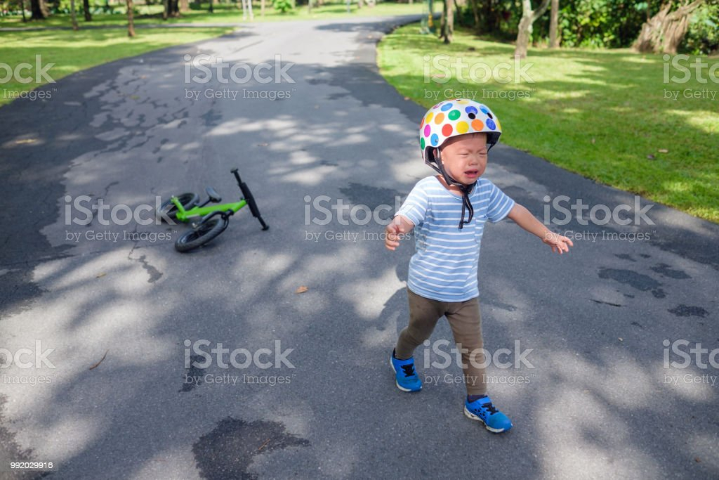 Cute upset stress sad unhappy little Asian 2 years old toddler baby boy child crying after fallen from his first bicycle stock photo