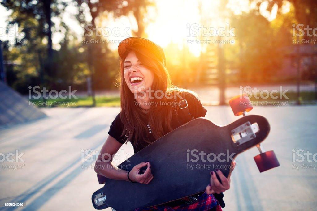 Cute urban girl holding skateboard in skatepark stock photo