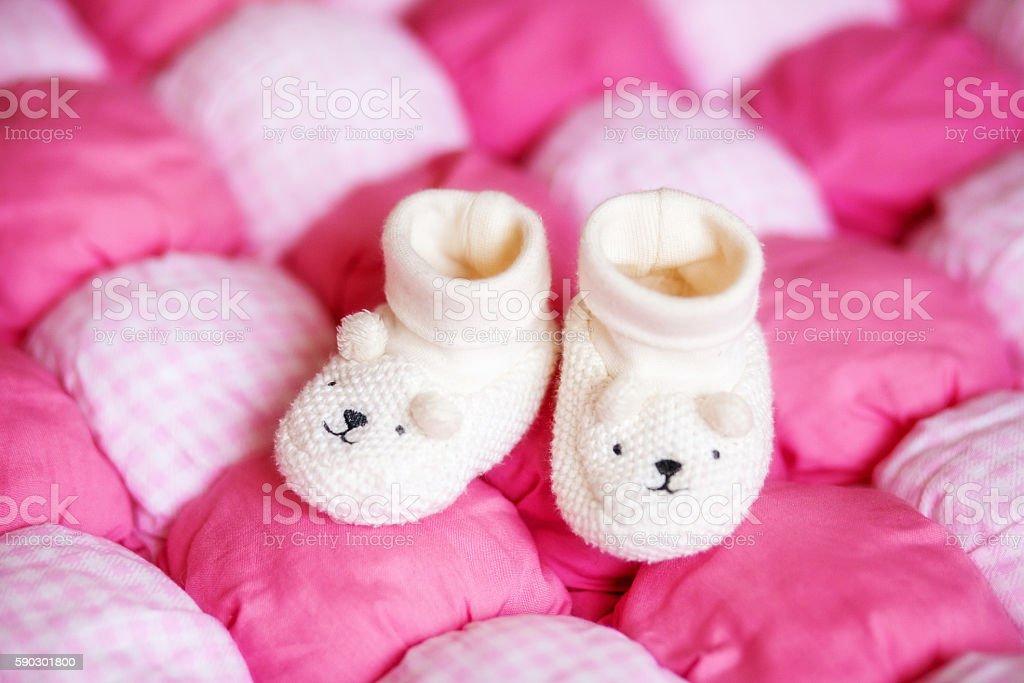 Cute white baby booties on pink blanket. Pregnancy concept Стоковые фото Стоковая фотография