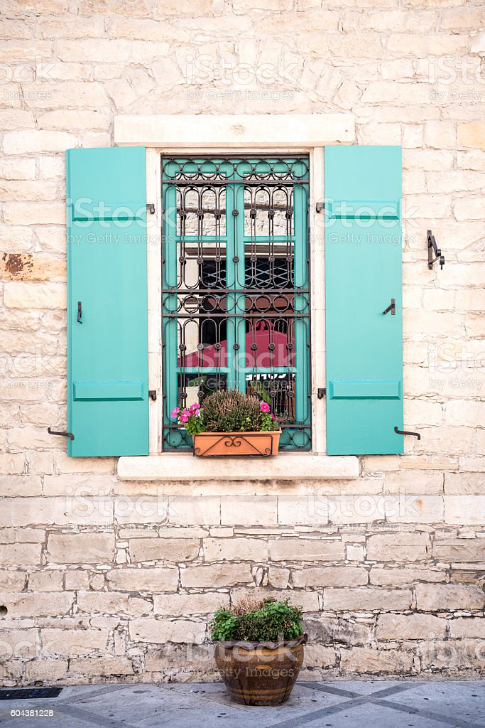 Cute window with blue shutters and flowers stock photo