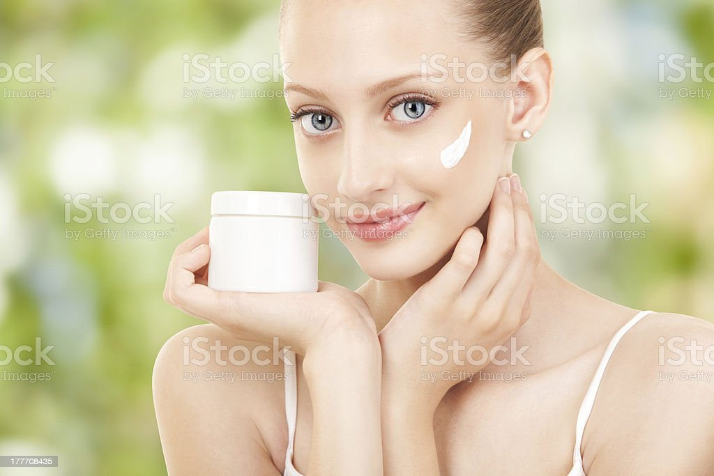 Cute woman applying cream to her face stock photo