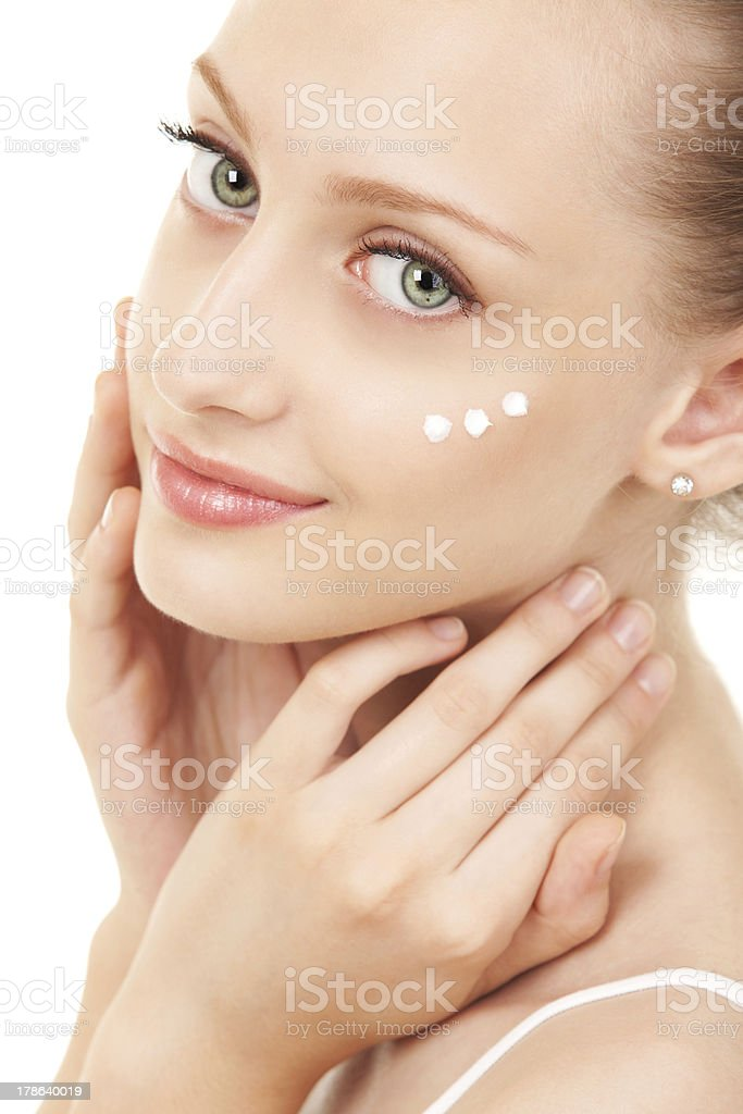 Cute woman applying cream to her face royalty-free stock photo
