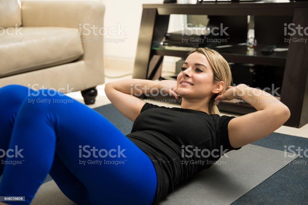 Cute woman doing crunches at home - foto de acervo