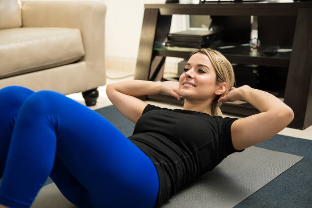 cute woman doing crunches at home - sit ups stock photos and pictures