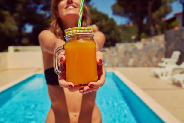 Cute woman drinking juice on the swimming pool. Summer concept. stock photo