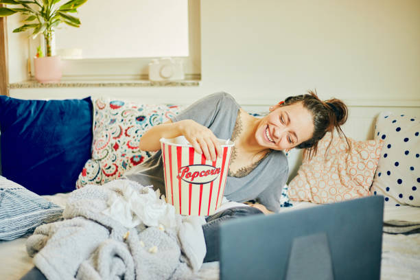 Cute woman eat popcorn and watching movie at home. stock photo