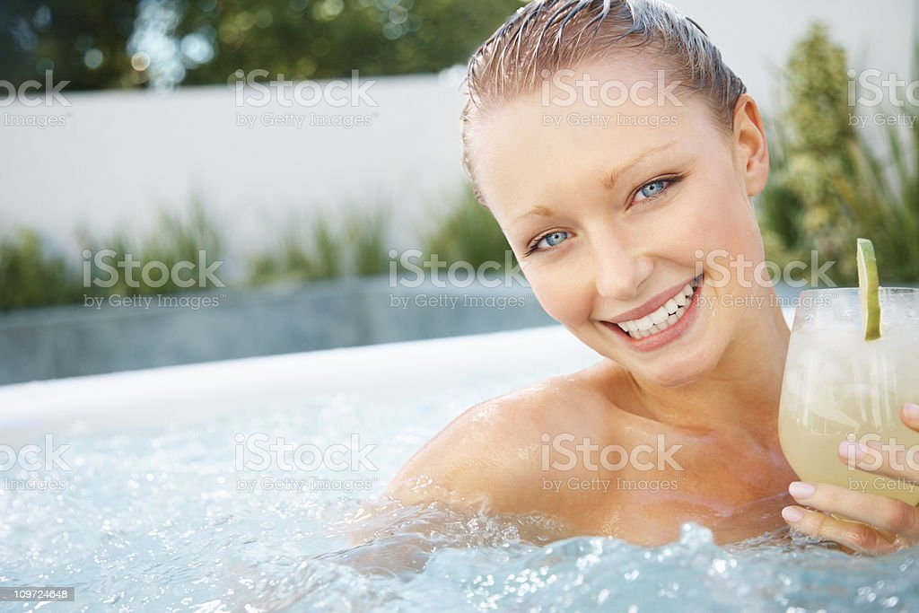 Cute woman enjoying a cocktail and the Jacuzzi royalty-free stock photo
