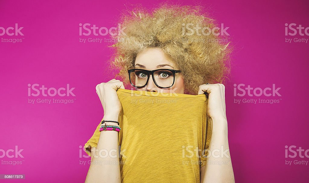 Cute woman in blonde afro hiding stock photo