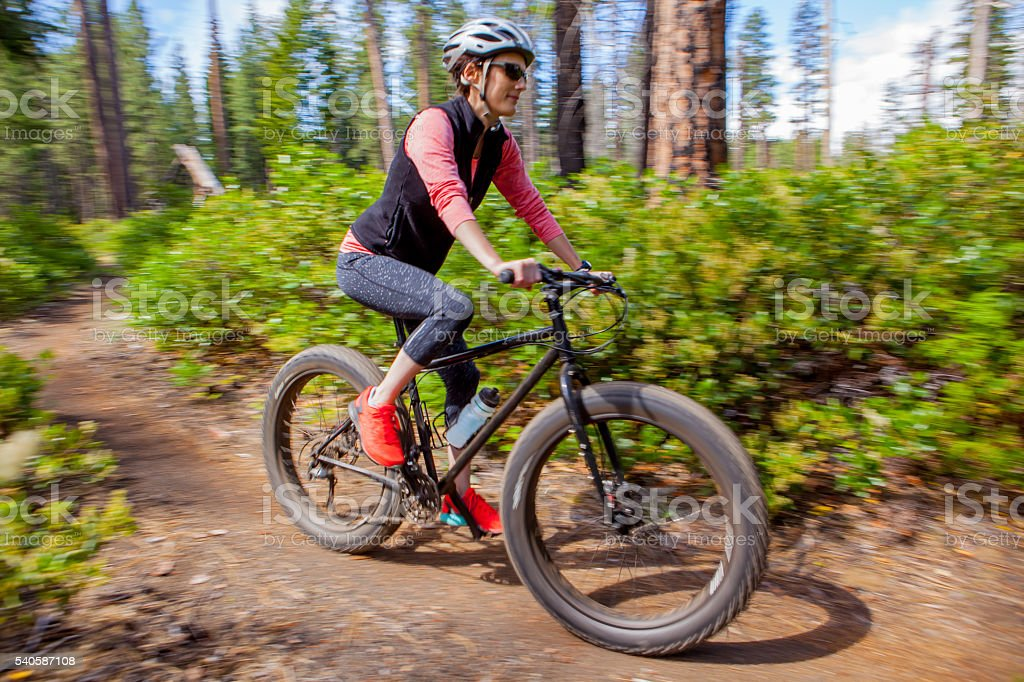 Cute woman in her thirties riding her fatbike in Oregon. stock photo