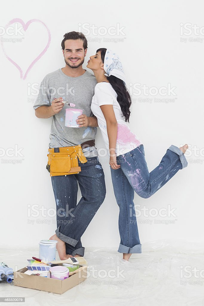 Cute woman kissing cheek of boyfriend holding paint pot royalty-free stock photo