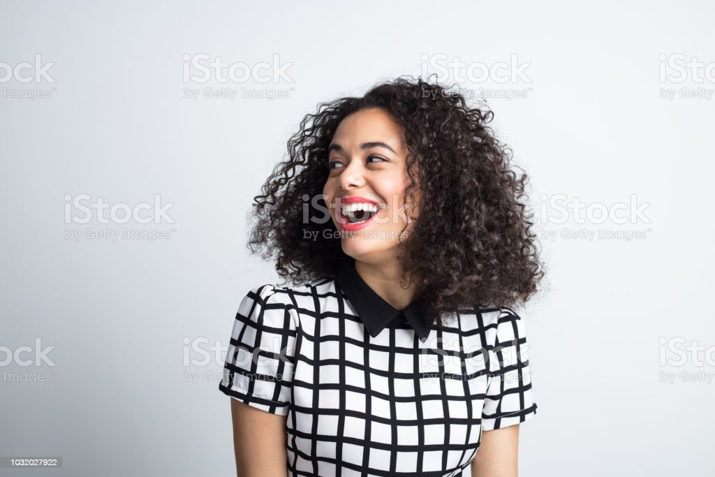 Cute woman looking away and laughing Close up portrait of cute young woman with curly hair looking away and laughing. Cheerful female model looking at copy space on gray background. 20-24 Years Stock Photo