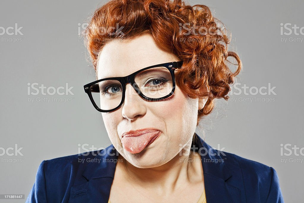Cute woman making face Portrait of cute young woman sticking out her tongue, looking at the camera. Studio shot, grey background. 25-29 Years Stock Photo