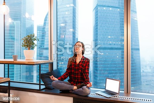 1162297213 istock photo Cute woman manager in casual clothes and glasses meditate during break next to laptop in the background of window overlooking the skyscrapers in the business center 958794006