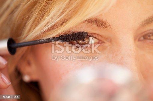 istock Cute  woman putting some mascara on 509811000