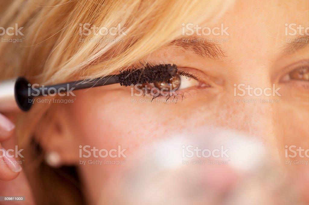 Cute  woman putting some mascara on stock photo