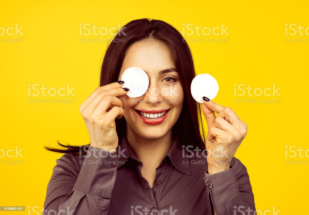 Cute woman removing applied makeup with a cotton sponge pad isolated on yellow background 'n stock photo