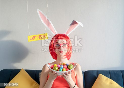 istock Cute woman wearing bunny ears on Easter day 1304340970