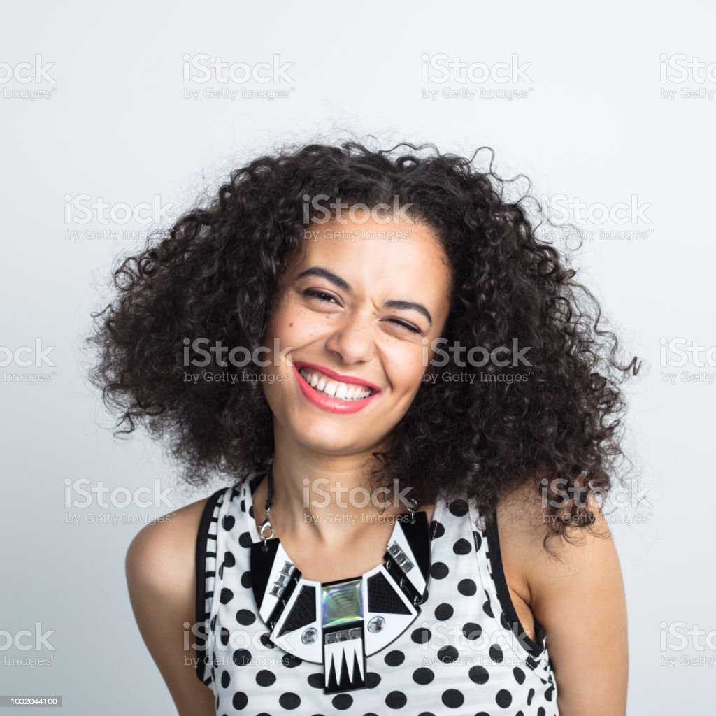 Cute woman winking with beautiful smile Close up portrait of attractive young woman with curly hair winking on white background 20-24 Years Stock Photo
