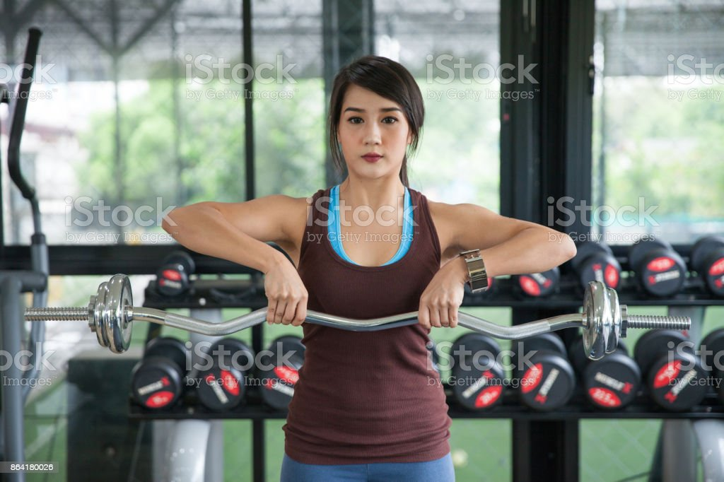 Cute woman with barbell flexing muscles in gym royalty-free stock photo