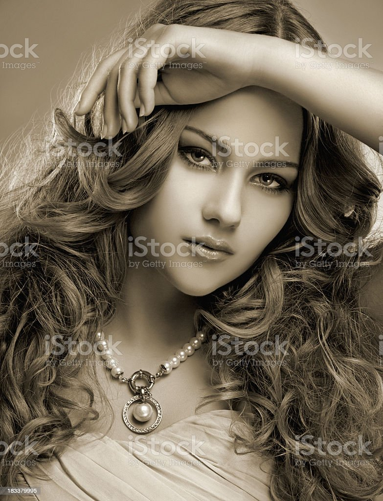 cute woman with curled long hair wearing pearl's necklace royalty-free stock photo