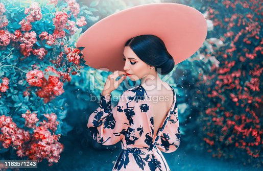 cute woman with perfect gentle hairdo from long black hair wearing pink hat with wide brim, elegant look for date and photo shoot, lady with open back and bright lips, girl in blooming roses.
