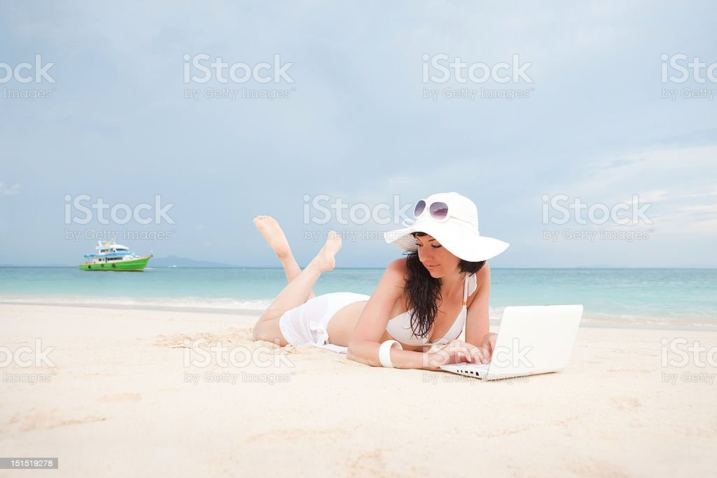 Cute woman with white laptop on the summer beach royalty-free stock photo