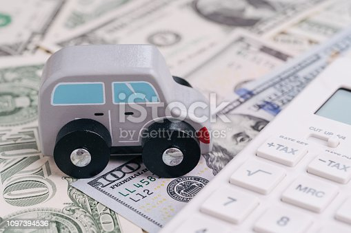 936987338 istock photo Cute wooden small toy car parking beside white calculator on pile of dollar banknotes money, car leasing, rental or insurance and maintenance calculation concept, down payment, installment for auto 1097394536