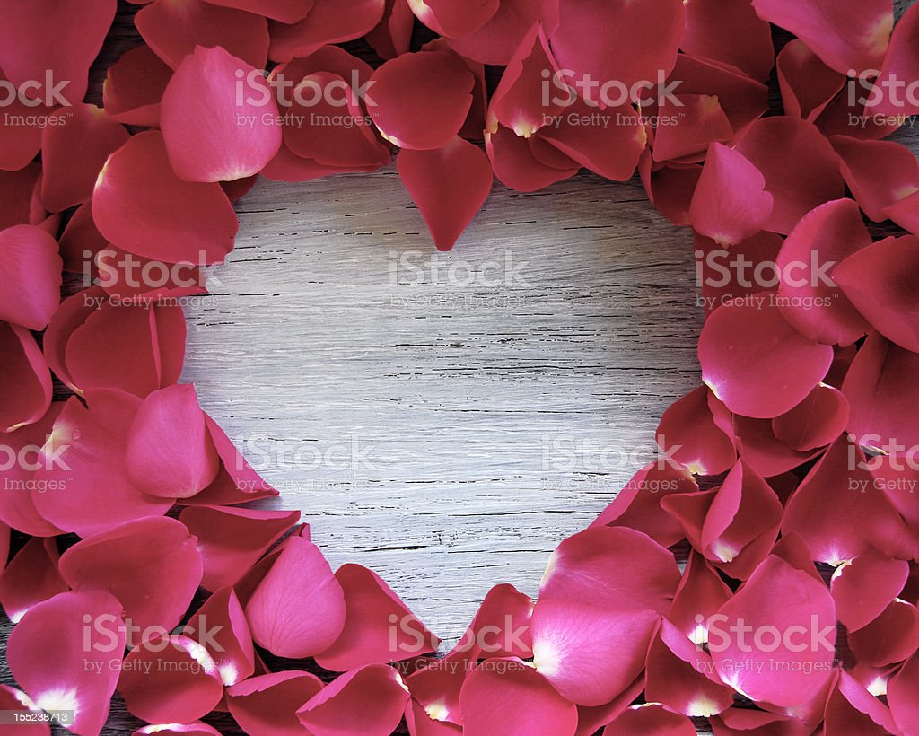Cute wooden white heart with rose petals stock photo