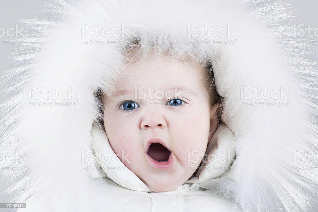 Cute yawning baby girl wearing huge white fur hat royalty-free stock photo