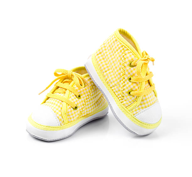 Cute yellow baby shoes with laces stock photo
