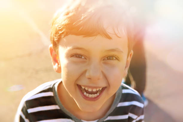 cute young 6-7 years old boy smiles, sunny lights, childhood concept cute young 6-7 years old boy smiles, sunny lights, childhood concept one boy only stock pictures, royalty-free photos & images