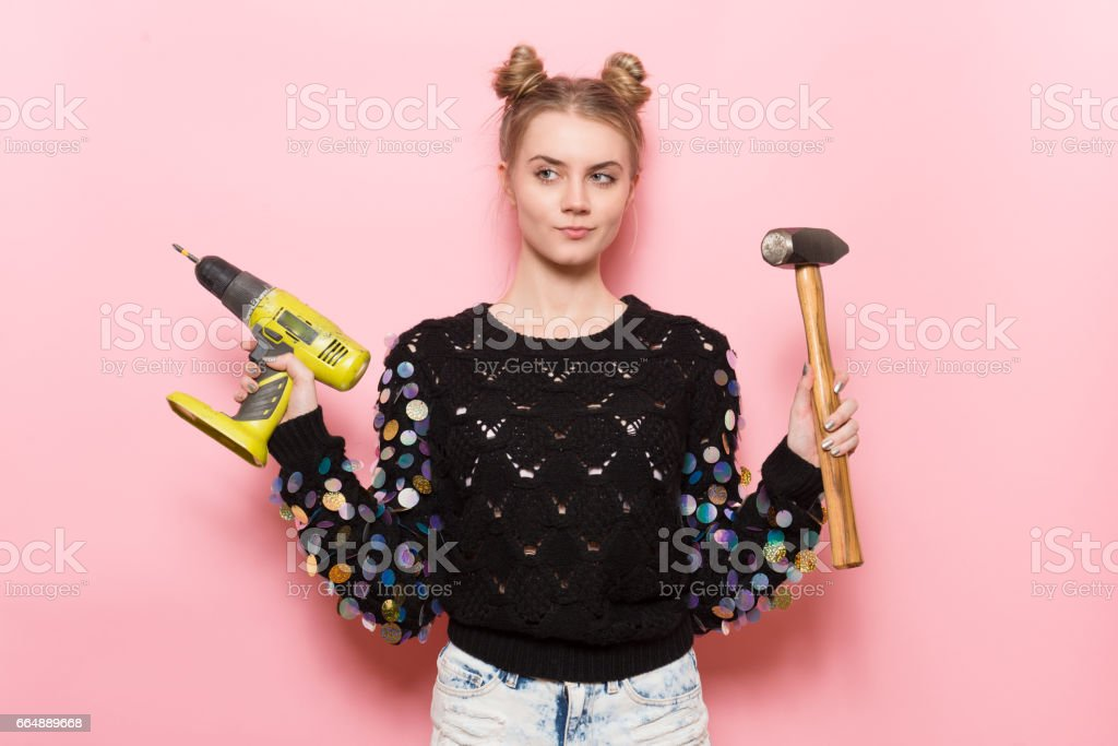 cute young adult woman holding working tools in hands stock photo