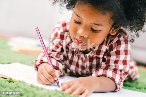 istock Cute young African American kid girl drawing or painting with colored pencil. Kindergarten children education, or preschool child study at home concept 1133425979
