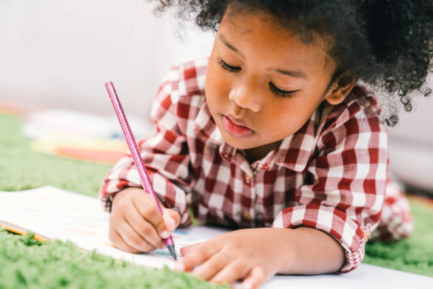 Cute young African American kid girl drawing or painting with colored pencil. Kindergarten children education, or preschool child study at home concept Cute young African American kid girl drawing or painting with colored pencil. Kindergarten children education, or preschool child study at home concept flourish art stock pictures, royalty-free photos & images