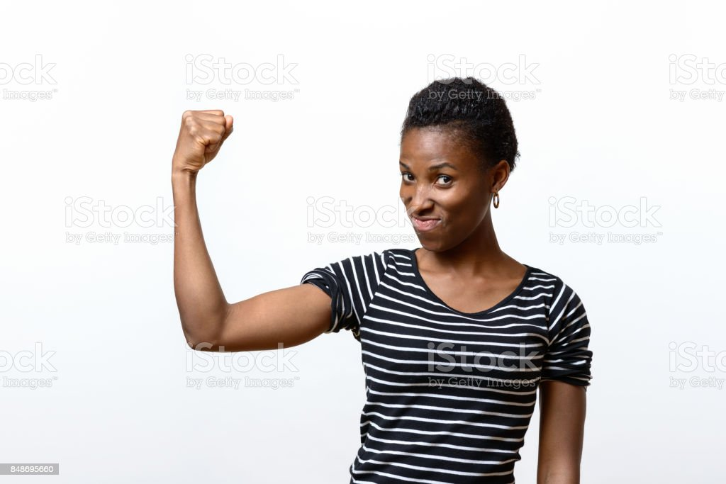 Cute young African woman flexing her muscles stock photo