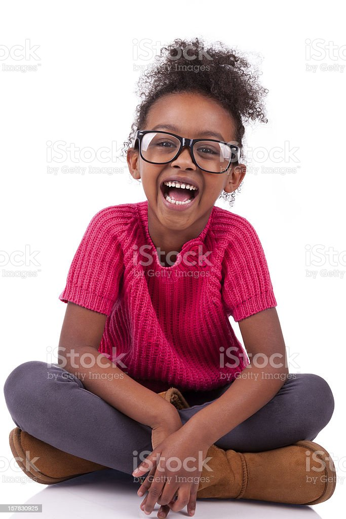 Cute young African-American girl sitting on floor smiling stock photo