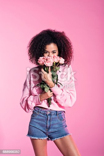 istock Cute young afro woman holding flowers 688966052