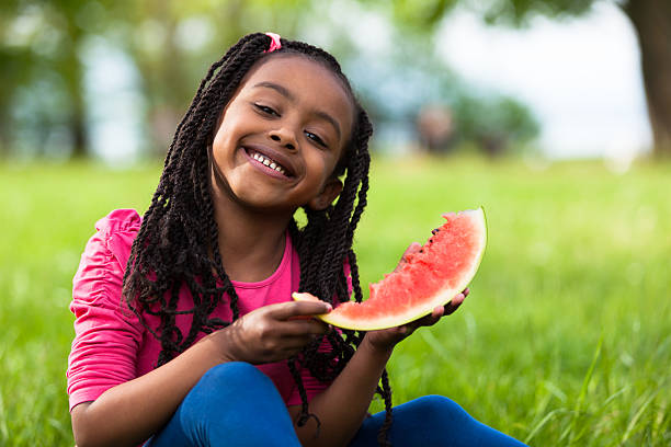 Cute young black little girl eating watermelon stock photo
