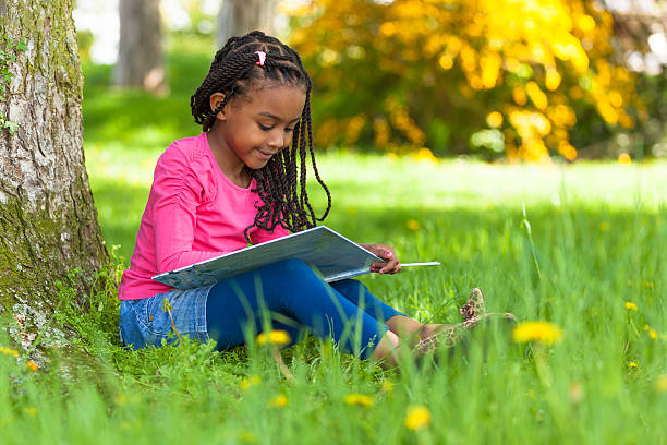 cute young black little girl reading a book - a little girl reading a book stockfoto's en -beelden