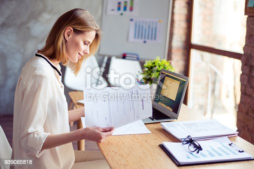 Cute young blond lady is concentreted on ideas for new start up. She is in casual shirt, sitting at her work place and studying documents